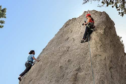 Zwei Personen klettern gesichert einen Felsen hinauf